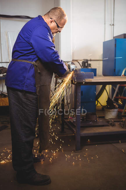 Welder sawing metal with electric tool in workshop — Stock Photo