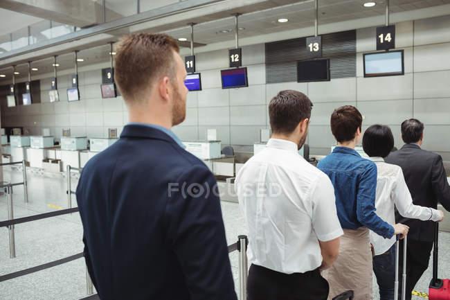 Пасажири, які очікують у черзі на реєстрації разом із авіаквитком з багажем всередині терміналу аеропорту — стокове фото
