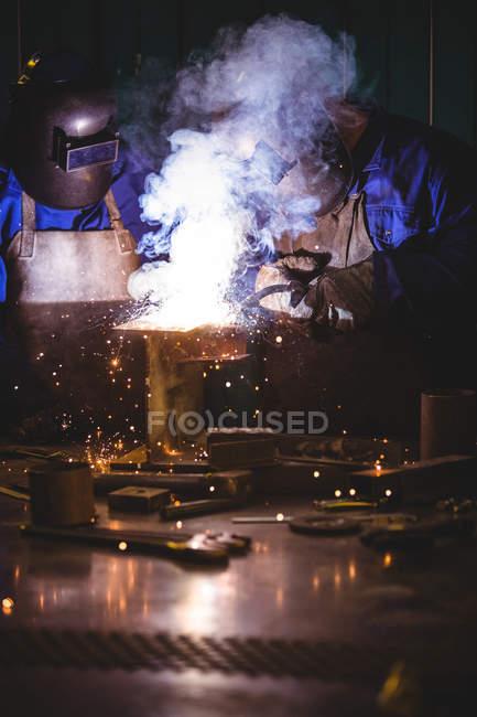 Welders welding metal in workshop — Stock Photo