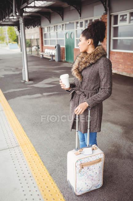 Femme tenant tasse de café jetable tout en se tenant debout à quai de la gare — Photo de stock