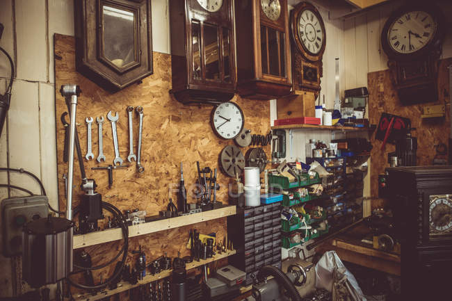 Antiguo taller de relojería con herramientas de reparación de relojes, equipos y relojes en la pared - foto de stock