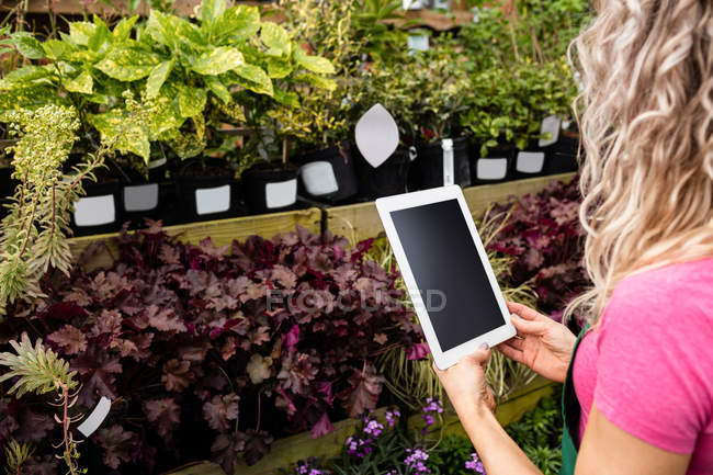 Female florist photographing potted plants in garden centre — Stock Photo