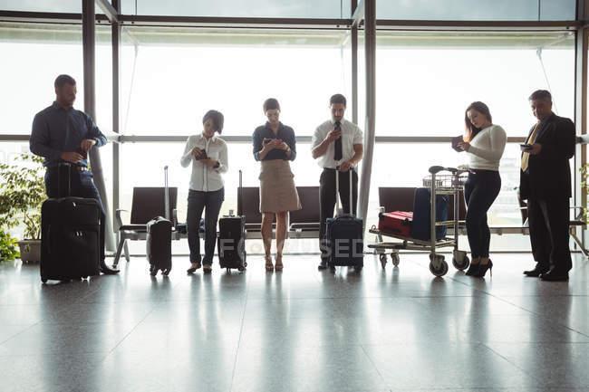 Деловые люди, использующие мобильные телефоны в зоне ожидания терминала аэропорта — стоковое фото
