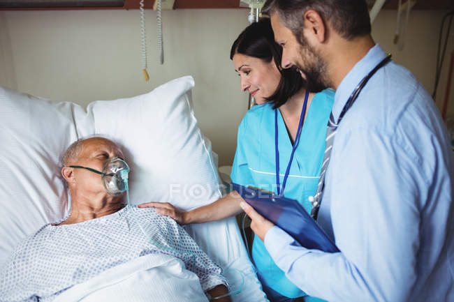 Nurse consoling senior patient with doctor in hospital — Stock Photo