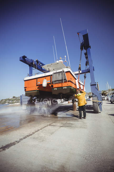 Man cleaning boat with pressure washer on sunny day — Stock Photo