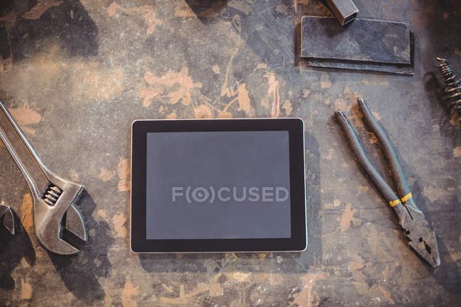 Top view of Digital tablet and tools on table in workshop — Stock Photo