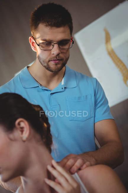 Fisioterapista che allunga il collo della paziente in clinica — Foto stock
