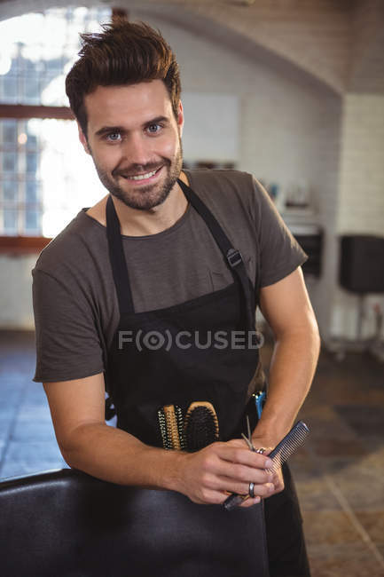 Portrait de coiffeur masculin tenant des ciseaux, peigne et brosse dans le salon — Photo de stock