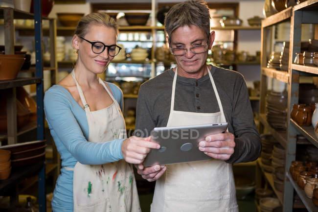 Lächelnde Töpfer mit digital-Tablette in Keramikwerkstatt — Stockfoto