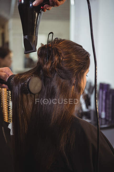 Back view of Woman getting her hair dried with hair dryer at hair salon — Stock Photo