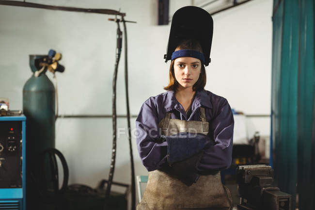 Portrait of female welder standing with arms crossed in workshop — Stock Photo