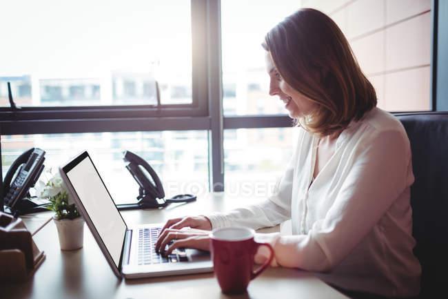Empresária trabalhando no laptop no escritório — Fotografia de Stock