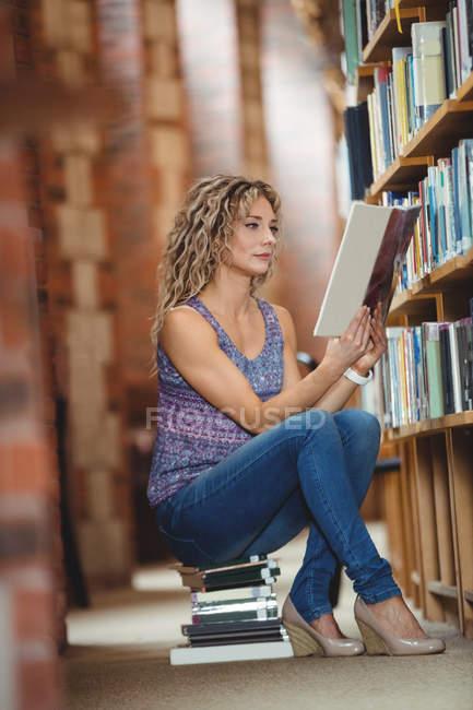 Femme assise et lecture du livre dans la bibliothèque — Photo de stock