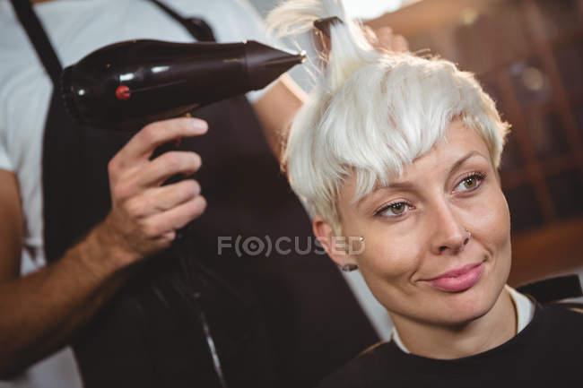 Sorrindo mulher recebendo seu cabelo seco no salão de cabeleireiro — Fotografia de Stock