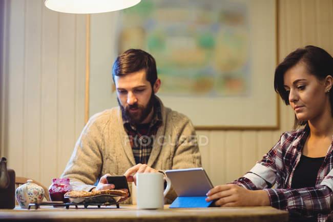Чоловік і жінка за допомогою цифрових планшетів і мобільний телефон вдома — стокове фото