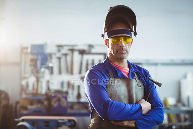 Portrait of handsome welder standing with arms crossed in workshop — Stock Photo