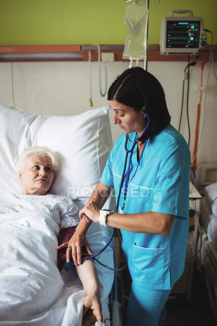 Krankenschwester überprüft Blutdruck von Seniorin im Krankenhaus — Stockfoto