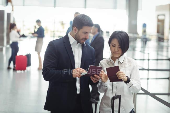 Деловые люди проверяют свои паспорта в терминале аэропорта — стоковое фото
