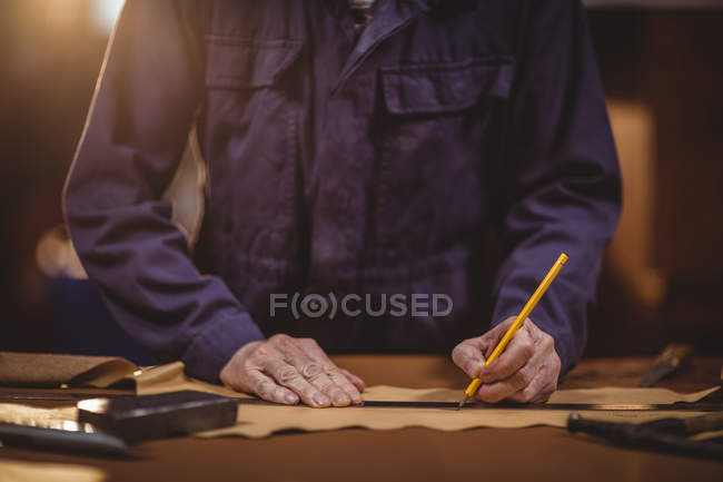 Mid section of shoemaker cutting a piece of leather in workshop — Stock Photo