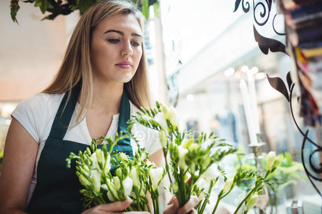 Female florist arranging flower in the flower shop — Stock Photo