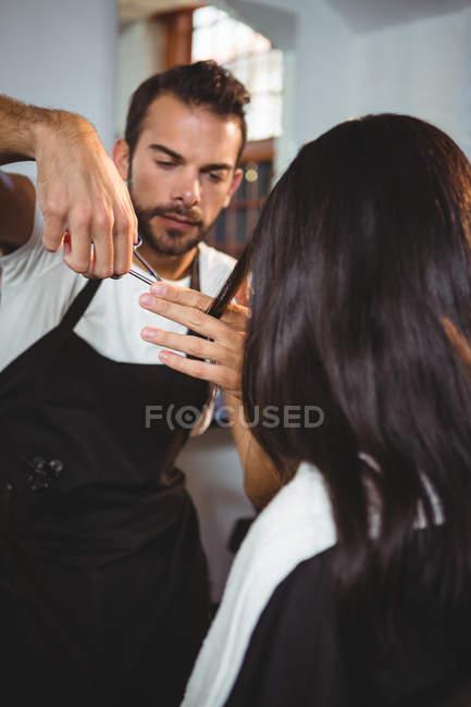 Mujer consiguiendo su pelo recortado con tijeras en el salón - foto de stock