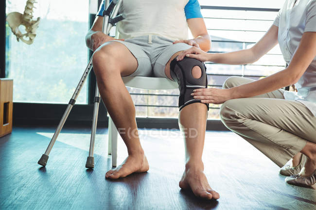 Imagen recortada de fisioterapeuta femenina examinando su rodilla paciente en la clínica - foto de stock