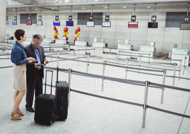 Business people waiting at check-in counter with luggage in airport terminal — Stock Photo
