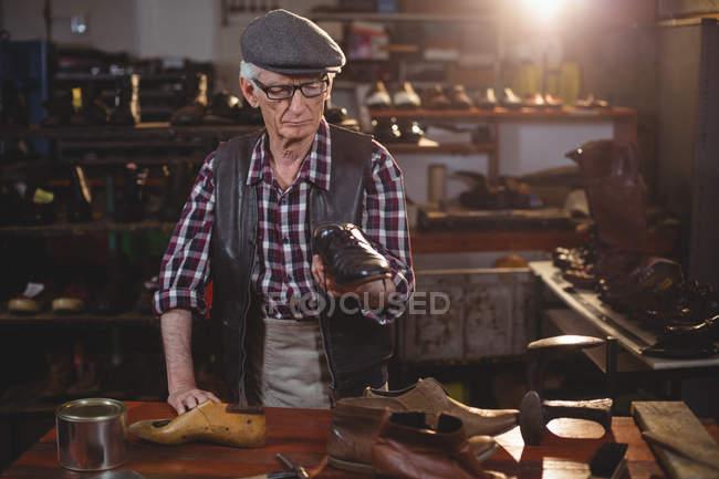 Senior shoemaker in cap examining a shoe in workshop — Stock Photo