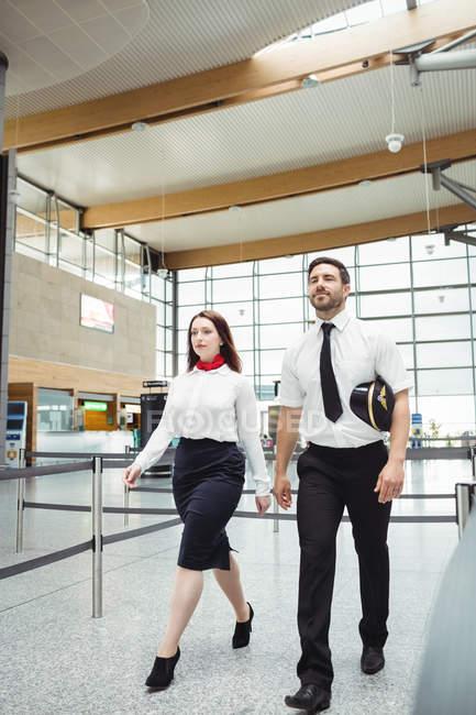 Piloto y azafata caminando en el aeropuerto - foto de stock