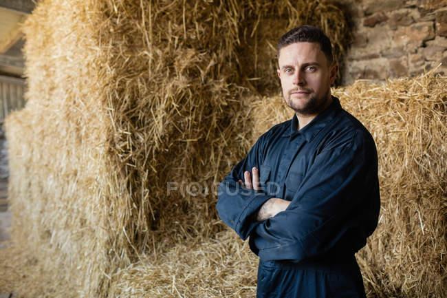 Porträt eines selbstbewussten Landarbeiters, der gegen Heuballen im Stall steht — Stockfoto
