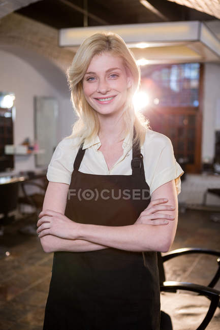Portrait of female hairdresser standing with arms crossed at salon — Stock Photo