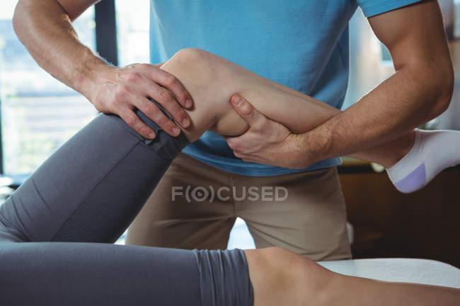 Обітнутого зображення чоловічого фізіотерапевт, даючи коліно масаж пацієнтки в клініці — стокове фото