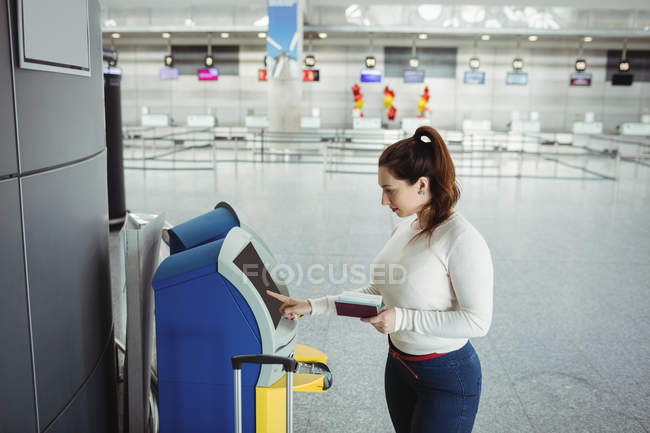 Traveller using self service check-in machine at airport — Stock Photo