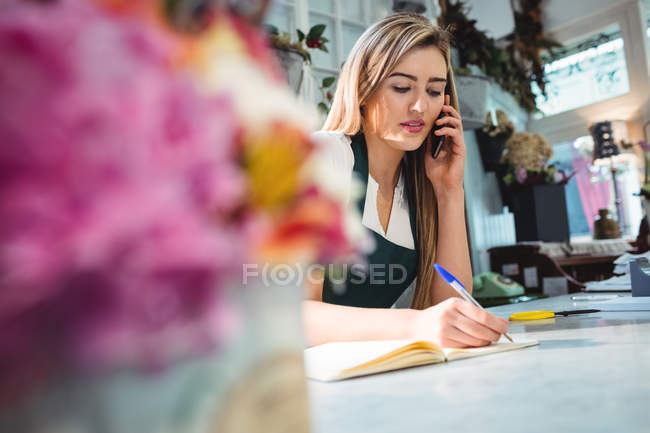 Floristería mujer teniendo orden de móvil en la tienda - foto de stock