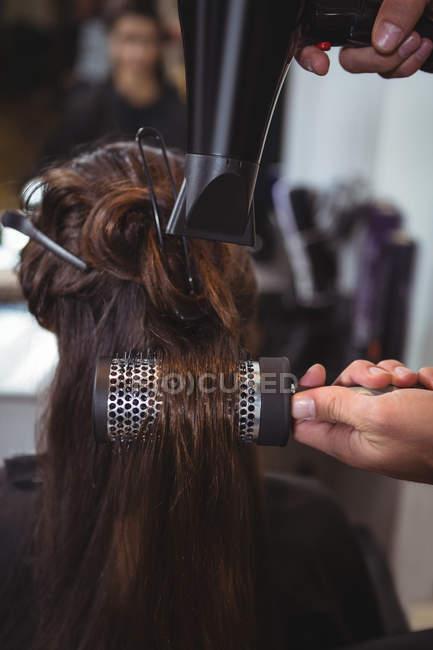 Vista posterior de la mujer conseguir su pelo secado con secador de pelo en peluquería - foto de stock