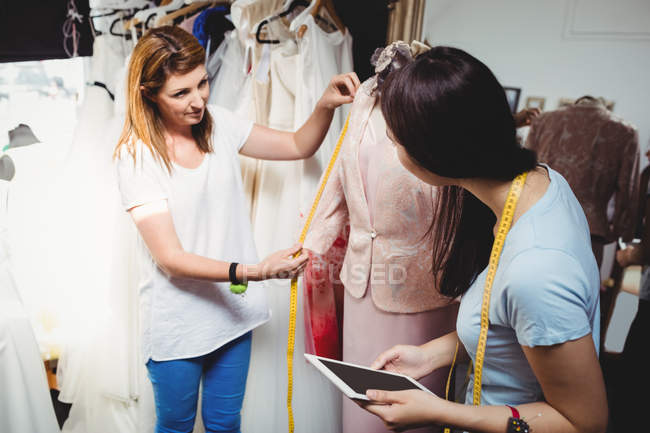 Female fashion designers working on laptop in studio — Stock Photo