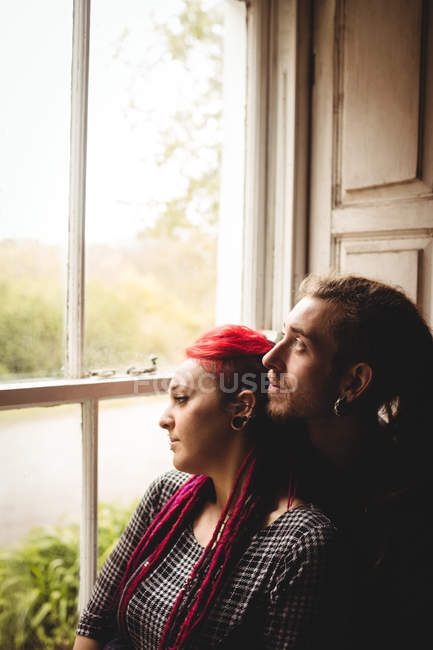 Young couple embracing while looking through window at home — Stock Photo