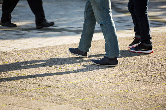 Low section of people walking on street in daylight — Stock Photo