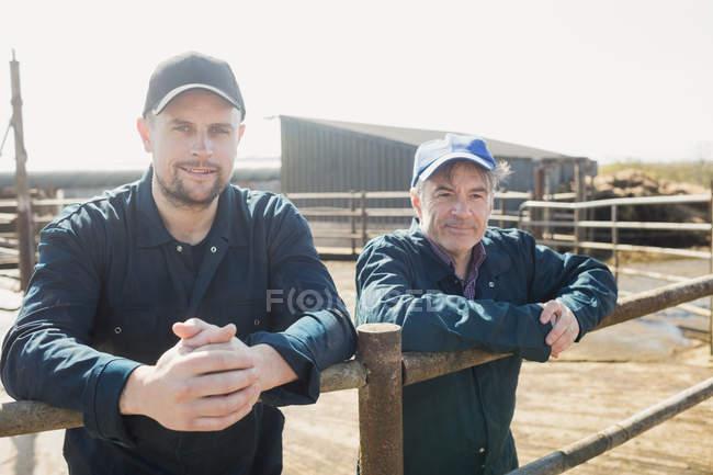 Ritratto di lavoratori agricoli fiduciosi appoggiati a recinzioni metalliche — Foto stock