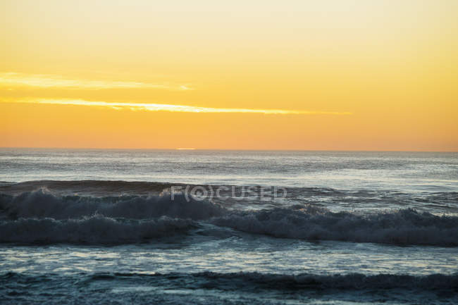 Захід сонця над хвилі на пляжі — стокове фото