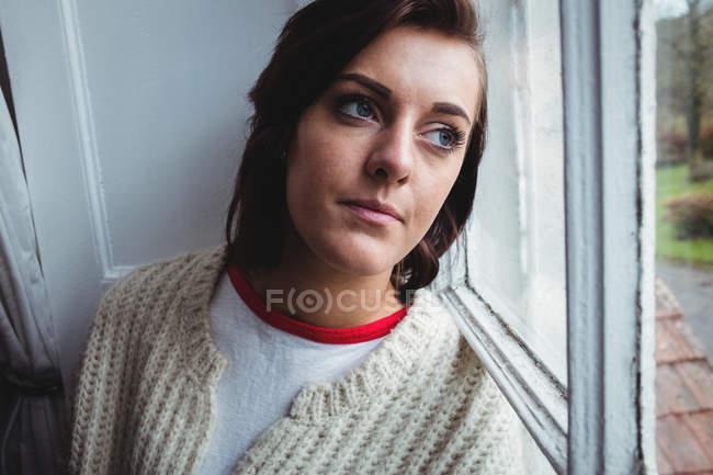 Mulher pensativa olhando através da janela em casa — Fotografia de Stock