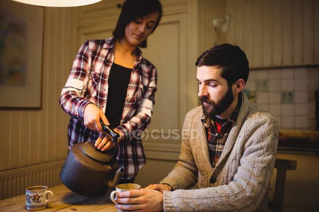 Frau, Gießen Tee mit einer Teekanne zu Hause — Stockfoto