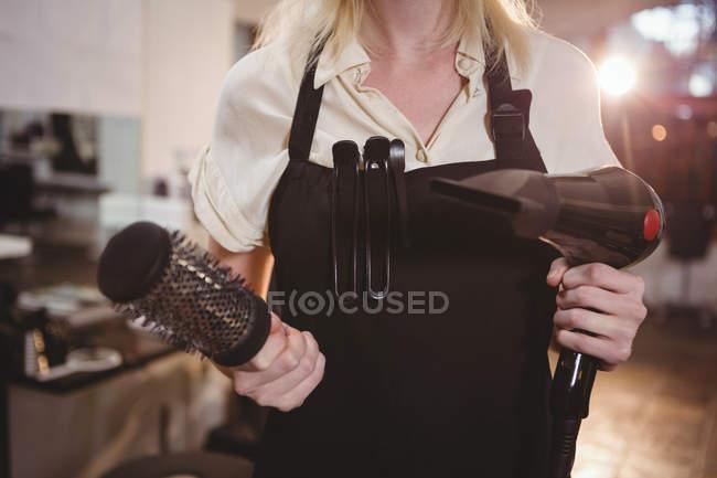 Milieu de coiffeuse tenant brosse et sèche-cheveux au salon de coiffure — Photo de stock