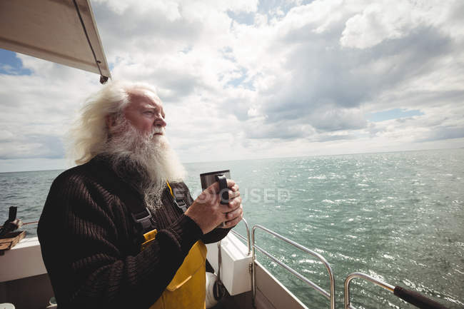 Nachdenklicher Fischer mit grauen Haaren, der mit einer Tasse Kaffee auf dem Boot steht — Stockfoto