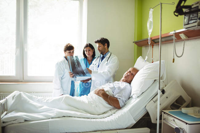 Doctors interacting over x-ray report with patient with patient in hospital — Stock Photo