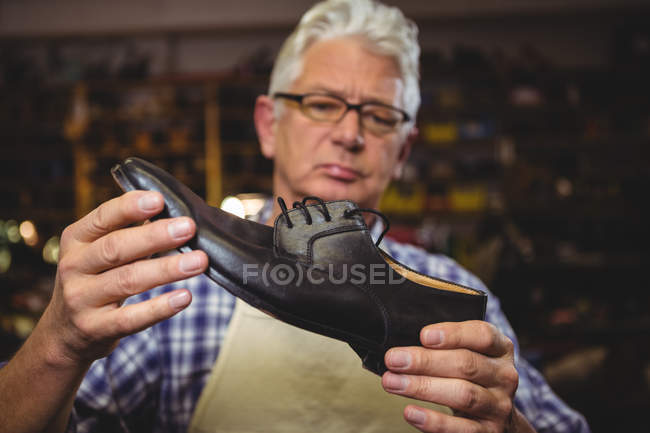 Mature shoemaker examining a shoe in workshop — Stock Photo