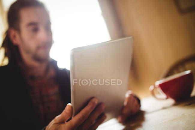 Uomo in possesso di tablet digitale a casa — Foto stock