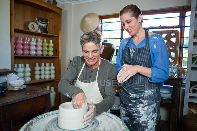 Male potter assisting female potter in pottery workshop — Stock Photo