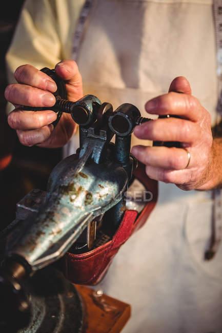 Hands of shoemaker using shoe stretcher machine in workshop — Stock Photo