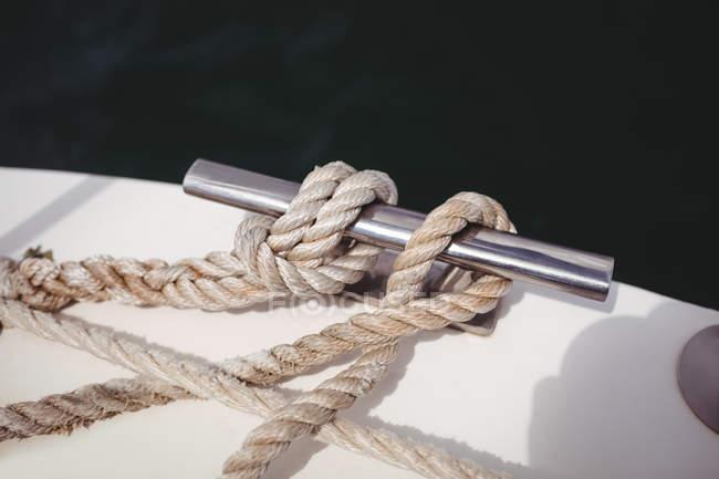 Крупный план веревки, привязанной к болларду на палубе лодки — стоковое фото
